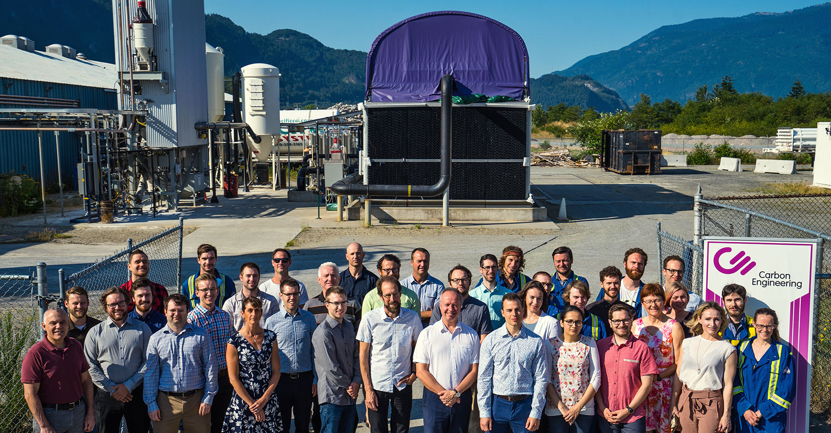 Carbon Engineering team members standing in front of direct air capture technology outside with Squamish's Howe Sound behind them.
