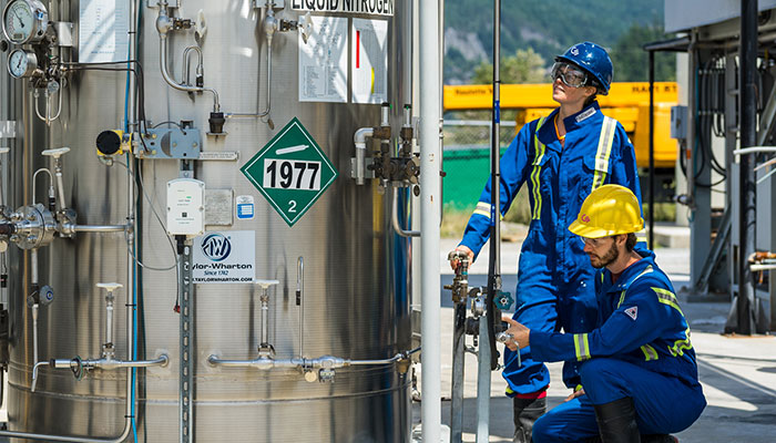 Two Carbon Engineering employees in blue coveralls take measurements outside at a direct air capture facility with mountains in the background and liquid nitrogen in the foreground.