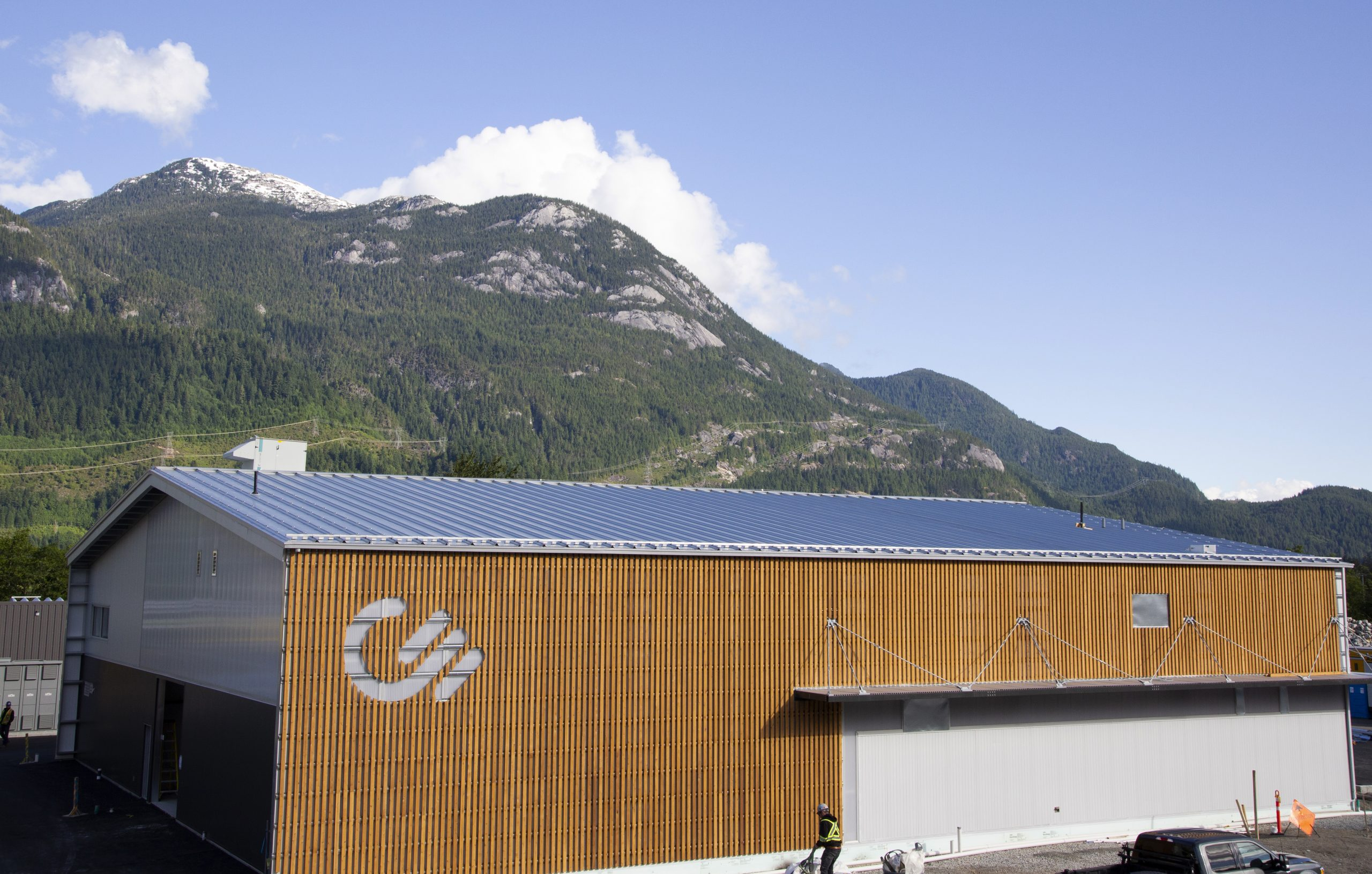 An image of wood paneling on the Carbon Engineering office building exterior, with a mountain and blue sky in the background.